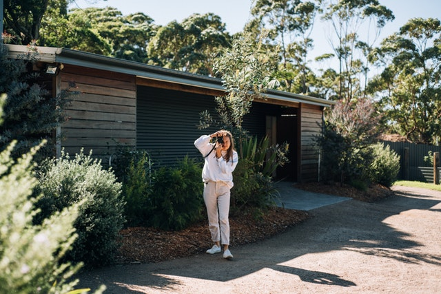 Žena, ktorá fotografuje pred malým, úzkym domom
