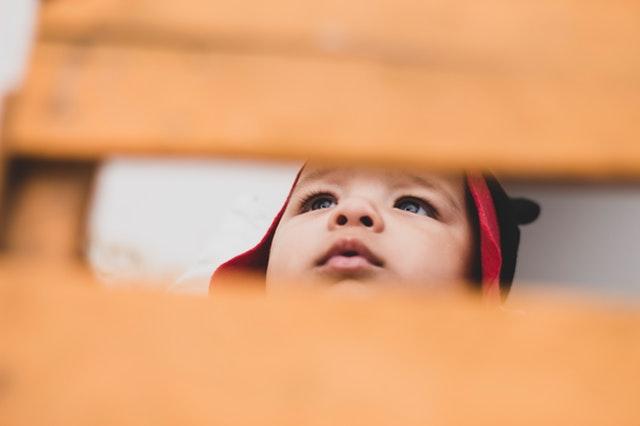 Bábätko v čiapke sa pozerá cez rám drevenej postieľky