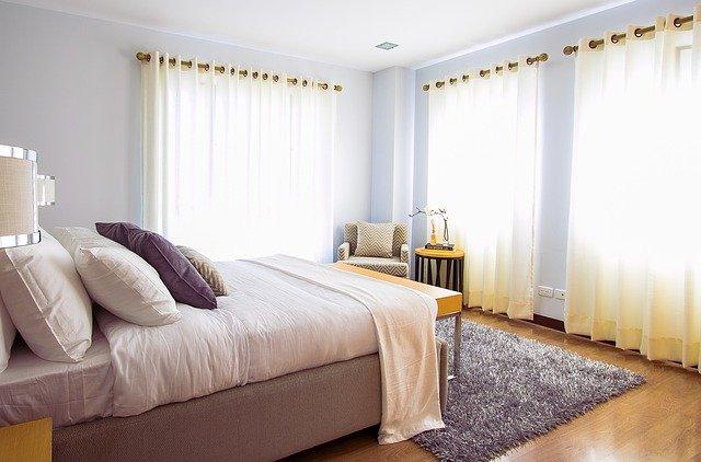 Spálňa s posteľou s veľkými tabuľami skla na stenách.jpg