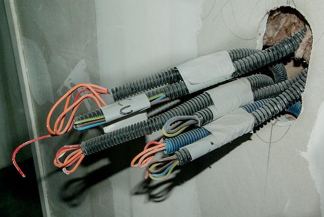 Elektrické káble v plastových chráničkách trčiace zo steny.jpg