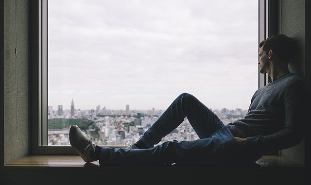 Muž pozerá cez okno, nuda